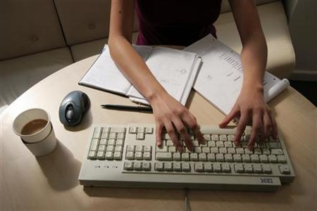 A generic picture of a woman working in an office sitting at her desk typing on a computer. REUTERS/Catherine Benson
