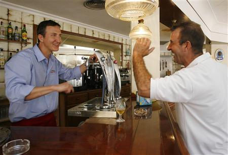 Co-owner Michal Lotocki (L) and a customer argue and insult each other in a friendly way at the 'Casa Pocho' bar in Cullera, near Valencia, June 18, 2009. The Spanish bar is encouraging clients to insult its staff and offering free drinks for original or hilarious abuse. Polish-born bar owner Bernard Mariusz said he thought people needed somewhere to release their frustrations at a time of economic crisis, employing the Spanish language's rich store of earthy obscenities. REUTERS/Heino Kalis