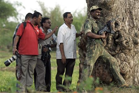 Media personnel and a police officer take cover behind a tree during a firefight between police and Maoists rebels at Bhimpur near Lalgarh, some 170 km (106 miles) west of the eastern Indian city of Kolkata, June 18, 2009. REUTERS/Jayanta Shaw