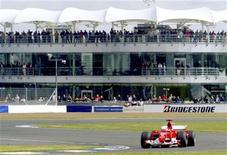 """<p>Пилот """"Феррари"""" Михаэль Шумахер проводит предварительный заезд по трассе в Сильверстоуне 10 июля 2004 года. Автогонки класса """"Формула-1"""" испытывают самые серьезные затруднения за последние 60 лет: восемь из десяти команд хотят создать независимый от оригинальной """"Формулы"""" чемпионат. REUTERS/Jed Leicester/Files</p>"""