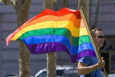 A man walks to City Hall holding a gay pride flag in San Francisco, California May 15, 2008. REUTERS/Kimberly White
