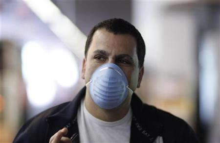 A passenger arriving from Mexico wears a mask at Frankfurt's airport, April 28, 2009. REUTERS/Johannes Eisele