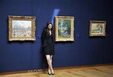 <p>Una empleada de la casa de subastas Christie's posa para los fotógrafos junto al cuadro de Claude Monet 'Au Parc Monceau' (al centro) en Londres, Gran Bretaña, jun 18 2009. REUTERS/Kieran Doherty (BRITAIN)</p>