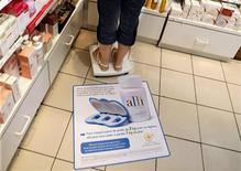 <p>Женщина стоит на весах в аптеке в Ницце 5 июня 2009 года. Небольшой излишек веса совсем не повредит, а наоборот, позволит прожить дольше, уверяют канадские исследователи, опубликовавшие результаты своих многолетних наблюдений в он-лайн журнале Obesity. REUTERS/Eric Gaillard</p>