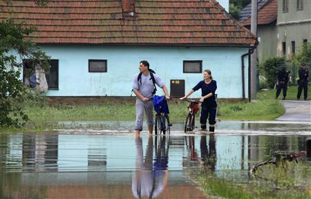 Residents push their bikes through a flooded street in Jesenik nad Odrou June 25, 2009. At least eight people died in overnight flooding in the eastern Czech Republic, police said on Thursday, and rising river levels prompted flood warnings across central Europe following heavy rains this week. REUTERS/Petr Josek