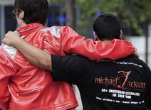 <p>Admiradores de Michael Jackson se abrazan fuera del estadio O2 Arena en Londres, sede donde Jackson planeaba realizar una serie de conciertos, 26 jun 2009. Junto con un vasto legado musical y legiones de seguidores, la superestrella del pop Michael Jackson dejó atrás una montaña de deudas y un regreso no concretado que muchos esperaban dejaría millones de dólares en taquilla y acabaría con sus problemas financieros. REUTERS/Nigel Roddis</p>