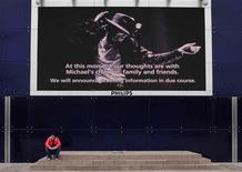 <p>Un admirador debajo de una pantalla con la imagen de Michael Jackson en el estadio O2 Arena en Londres, 26 jun 2009. La repentina muerte de Michael Jackson podría suponer un revés importante para AEG Live, promotora de su largamente esperada gira de 50 conciertos en Londres, así como para los fans que pagaron precios altos por las codiciadas entradas. Las actuaciones en el O2 Arena iban a empezar el 13 de julio, y los organizadores aún tienen que decidir exactamente cómo gestionan la devolución de las entradas compradas directamente a ellos mismos o en los establecimientos autorizados. REUTERS/Nigel Roddis</p>