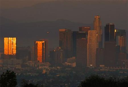 The sun reflects on downtown skyscrapers as it sets through the Los Angeles smog and haze in this October 22, 2006 file photo. REUTERS/Lucy Nicholson