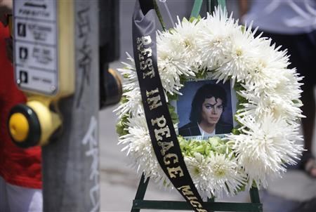 Michael Jackson fans leave flowers and wreaths at a makeshift memorial across the street from the County of Los Angeles Department of Coroner facility in Los Angeles June 26, 2009. REUTERS/Phil McCarten