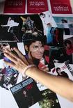 <p>Un fan tocca alcune immagini di Michael Jackson durante una commemorazione a Shangai. REUTERS/Aly Song</p>