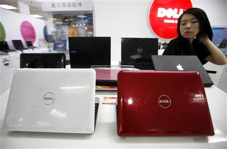 A Chinese saleswoman stands behind a row of Dell computers at a computer market in Beijing June 29, 2009. REUTERS/David Gray
