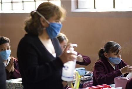 A teacher hands out disinfectant as schoolchildren wearing surgical masks attend class at an elementary school in Mexico City May 11, 2009. REUTERS/Jorge Dan