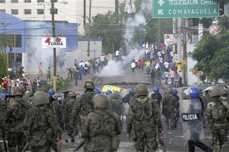 Supporters of Honduras' ousted President Manuel Zelaya run after soldiers and police fired tear gas during a protest in Tegucigalpa June 29, 2009. REUTERS/Oswaldo Rivas
