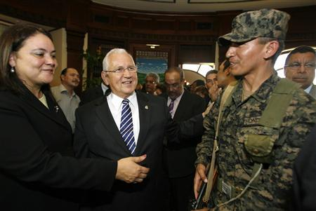 Honduras' interim President Roberto Micheletti (C) stands with newly appointed Economy Minister Gabriela Nunez (L) and an unidentified soldier after being sworn in at Congress in Tegucigalpa June 29, 2009. REUTERS/Oswaldo Rivas