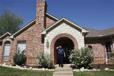 Realtor Rick Cumins walks down the steps of a house that has been on the market for two and a half years, in Cleburn, Texas March 24, 2009. REUTERS/Jessica Rinaldi