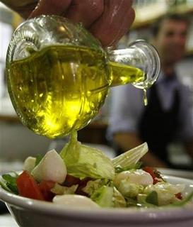 A diner pours olive oil on a salad at a restaurant in Rome May 17, 2007. REUTERS/Dario Pignatelli