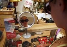 <p>A woman looks at a pair of sunglasses in a mirror while shopping for second-hand goods at a Housing Works store in New York June 26, 2009. REUTERS/Jamie Fine</p>