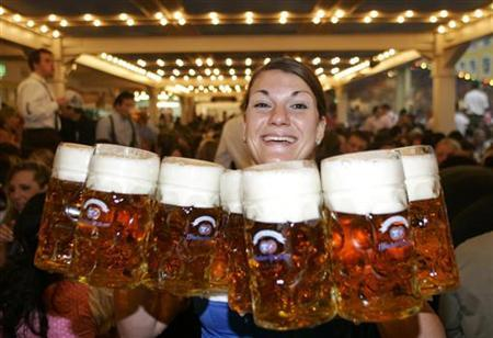 Waitress Marion Neumeyer carries one-litre beer mugs during the opening day of the Oktoberfest in Munich September 17, 2005. WORLD CUP 2006 PREVIEW REUTERS/Michaela Rehle/File photo