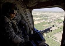 """<p>Солдат армии США наблюдает за местностью с борта вертолета Chinook, патрулирующего горную цепь в афганской провинции Вардак 1 июля 2009 года.Тысячи американских морских пехотинцев начали в четверг операцию в долине афганской реки Гильменд - самую крупномасштабную военную акцию за время президентства Барака Обамы - осуществив бросок в глубокий тыл занимаемой """"Талибаном"""" территории. REUTERS/Shamil Zhumatov</p>"""