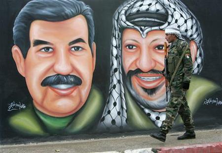 A member of the Palestinian security forces walks past a mural depicting the late Palestinian leader Yasser Arafat (R) and the late Iraqi president Saddam Hussein in the West Bank city of Jenin January 22, 2008. REUTERS/Mohamad Torokman