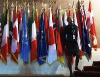 """<p>Женщина стоит у флагов различных государств и организаций на встрече министров иностранных дел """"Большой восьмерке"""" в Триесте 26 июня 2009 года. Италия пригласила представителей 40 стран и международных организаций, на чью долю приходится 90 процентов мировой экономики, на предстоящий на следующей неделе саммит """"Большой восьмерки"""", пытаясь сделать его более актуальным на фоне смещения акцентов на мировой экономической арене. REUTERS/Nikola Solic</p>"""