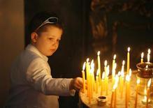 <p>Девочка зажигает свечу в православном храме в Стамбуле 19 апреля 2009 года. Что случится, если поместить в одной комнате имама, христианского священника, раввина, буддистского монаха и 10 атеистов? REUTERS/Osman Orsal</p>
