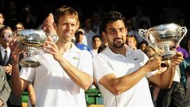 <p>Daniel Nestor of Canada (L) and Nenad Zimonjic of Serbia hold their trophies after defeating Bob and Mike Bryan of the U.S. in their Men's Doubles finals match at the Wimbledon tennis championships in London, July 4, 2009. REUTERS/Toby Melville</p>