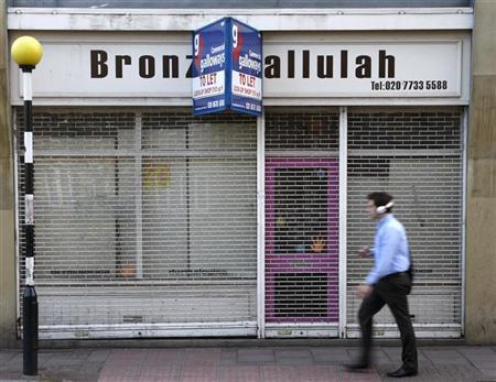 A pedestrian passes a closed down shop in Brixton in London April 24, 2009. REUTERS/Luke MacGregor
