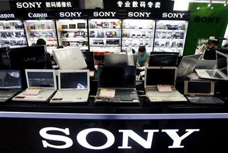 Chinese sales staff talk with customers behind a row of Sony computers for sale at a computer market in Beijing June 29, 2009. REUTERS/David Gray