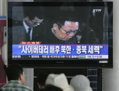 People watch a television news broadcast about hacker attacks at the Seoul railway station July 8, 2009. REUTERS/Choi Bu-Seok