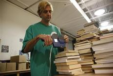 <p>Scott Duncan prices books at Half Price Books where he works in Dallas, Texas July 7, 2009. REUTERS/Jessica Rinaldi</p>