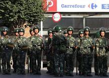 <p>Китайские солдаты у входа в магазин Carrefour в центре Курумчи 10 июля 2009 года. Спецподразделения китайской полиции разогнали небольшую демонстрацию, устроенную уйгурами в столице Синьцзян-Уйгурского автономного района в пятницу, арестовав несколько её участников. REUTERS/David Gray</p>