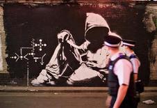 <p>Полицейские проходят мимо стены с граффити в Лондоне 23 июня 2008 года. Специализированный веб-сайт Travel and Leisure (http://www.travelandleisure.com) составил список самых красивых городов в плане уличного искусства - граффити на городских сооружениях, стенах и тротуарах. REUTERS/Finbarr O'Reilly</p>
