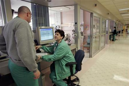 Critical care nurses David Levy (L) and Jean Isaac (C) confer in the intensive care unit of Tulane University Hospital in New Orleans February 14, 2006. REUTERS/Lee Celano