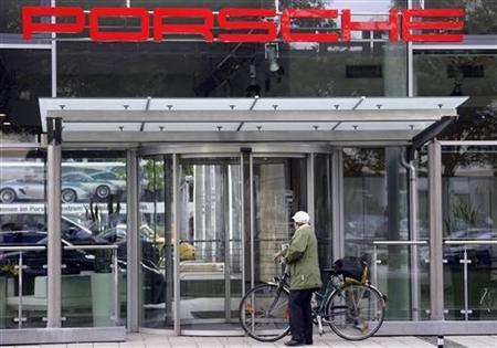 A unidentified pedestrian walks past an entrance of a Porsche car dealer in Munich June 22, 2009. REUTERS/Michael Dalder