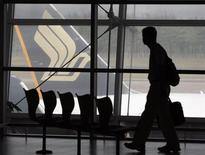 <p>A man walks in a viewing lounge facing a Singapore Airlines (SIA) aircraft at Singapore's Changi Airport May 13, 2008. REUTERS/Vivek Prakash</p>