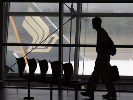 A man walks in a viewing lounge facing a Singapore Airlines (SIA) aircraft at Singapore's Changi Airport May 13, 2008. REUTERS/Vivek Prakash