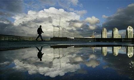 Storm clouds begin to clear over the surrounding mountains after leaving plenty of rain on ground in Vancouver, British Columbia at sunset October 9, 2003. REUTERS/Andy Clark