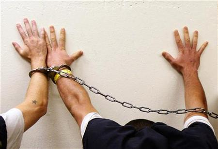 Prisoners place their hands on a wall as they are brought to jail by Orange County sheriff's deputies in Fullerton, California, June 23, 2009. REUTERS/Lucy Nicholson
