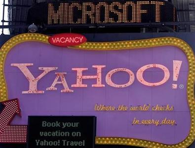 A Microsoft news headline runs across a news ticker above a Yahoo sign in New York City, May 19, 2008. REUTERS/Joshua Lott