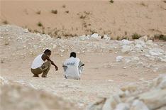 <p>Due migranti nigeriani in un'area di confine con Israele, sul Sinai, in attesa di varcare la frontiera. La foto è stata scattata nell'agosto 2008. REUTERS/Asmaa Waguih</p>