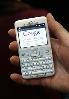 In this file photo a hostess holds a prototype of the Google Android mobile by British chip designer ARM during the Mobile World Congress (formerly 3GSM World Congress) in Barcelona, February 11, 2008. Google Inc is planning to include support for business users in its Android platform as soon as this year pitting it against BlackBerry maker Research In Motion, Android developer Andy Rubin said on Friday. REUTERS/Albert Gea