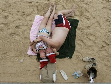 A couple share a siesta on Manly Beach in Sydney, December 25, 2007. REUTERS/Will Burgess