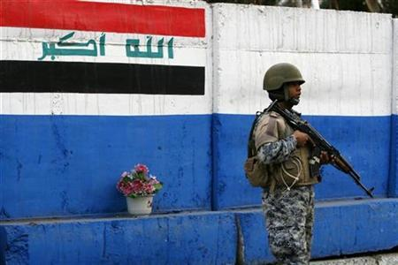 An Iraqi policeman stands guard in front of painted blast walls at a checkpoint in Baghdad January 18, 2009. REUTERS/Bassim Shati