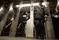 <p>Riders make their way through turnstiles at the Times Square subway station after service resumed in New York early December 23, 2005. REUTERS/Keith Bedford</p>