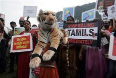 """<p>Митингующие держат плакаты и игрушечного тигра в поддержку """"Тамильских тигров"""" из Шри-Ланки недалеко от Куала-Лумпур 24 мая 2009 года. Лидер повстанческой группировки """"Тигры освобождения Тамил-Илама"""" (""""Тамильские тигры"""") Селвараджа Патманатан был задержан в четверг военными, сообщили власти Шри-Ланки. REUTERS/Bazuki Muhammad</p>"""