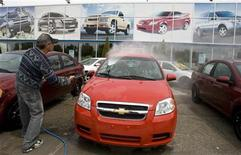 <p>A worker cleans automobiles at a General Motors dealership in Montreal, June 1, 2009. Reuters/Christinne Muschi</p>