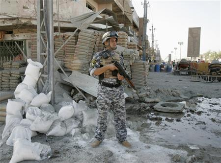 An Iraqi policeman stands guard at the site of a bomb attack in Baghdad's Amil district August 10, 2009. REUTERS/Bassim Shati