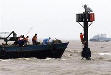 <p>Спасатели вытаются достать мужчину, который спасается на вышке от наводнения, вызванного тайфуном Моракот в Шанхае 9 августа 2009 года. Тайфун Моракот обрушился в воскресенье на побережье Китая. Жертвой стихии стал ребенок; несколько домов разрушены. REUTERS/Stringer</p>