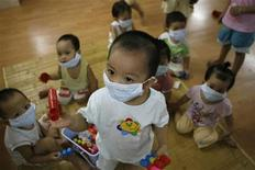 <p>Children wear protective masks at a kindergarten in Hanoi August 7, 2009. REUTERS/Kham</p>